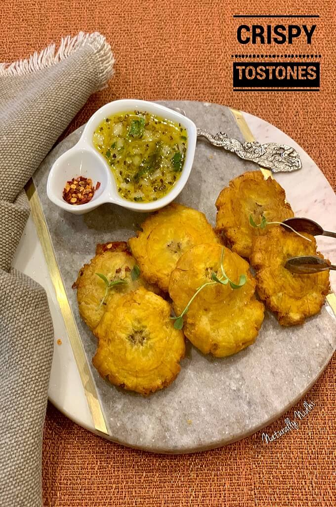Tostones (fried plantains) - a delicious street food from the Caribbean and Latin America! Fry them to perfection and serve them with an orange-based Cuban Mojo dipping sauce for a delicious appetizer or snack!