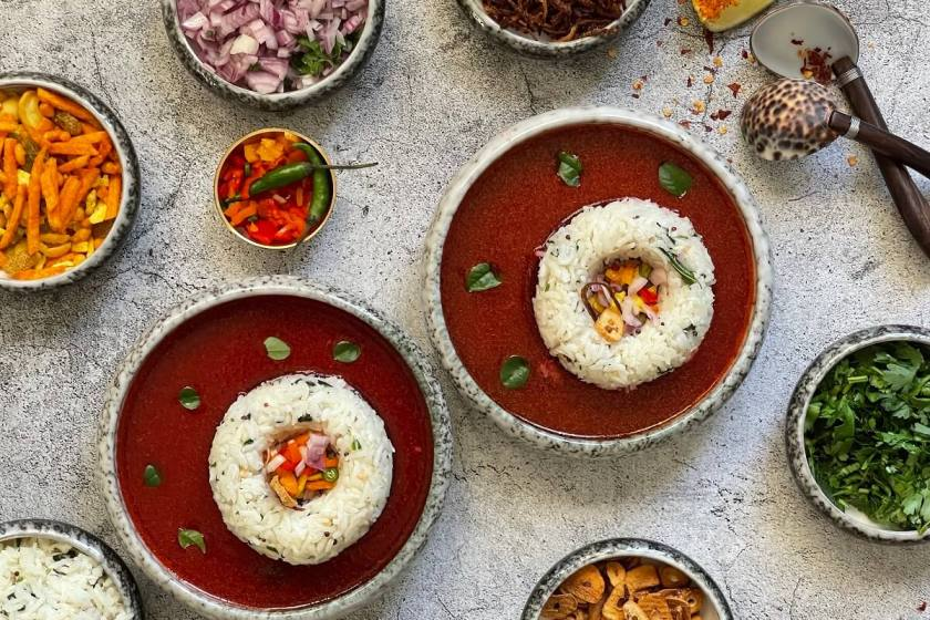 Tomato Beetroot Rasam with Coconut Rice - topped off with crunchy peanuts, fresh onions, crispy garlic and spicy namkeen to provide a burst of amazing flavors that take this traditional south indian soup to the next level!