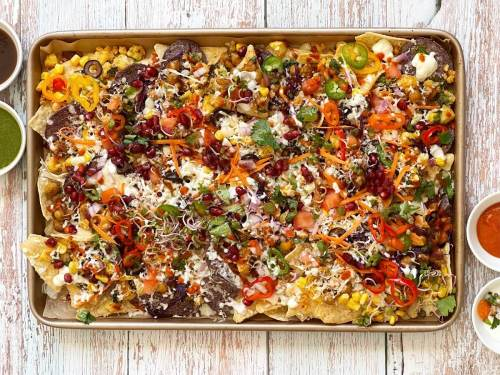 This Indian-style Chatpata Loaded Nachos features a cheesy-gooey texture with the goodness of crispy vegetables and flavorful spices. This new take on nachos draws inspiration from Indian chaat, with spicy masala and tangy chutneys. Be it a lazy evening snack or a light meal, this Indian twist on the beloved classic is a must-have.