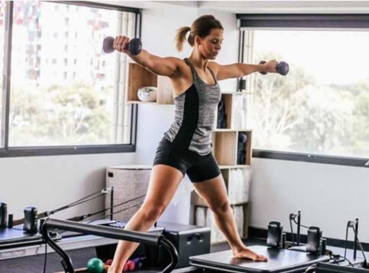A woman working out on Pilates Megaformer equipment as an example of Fitness Trends in 2020 that mix fun with results.