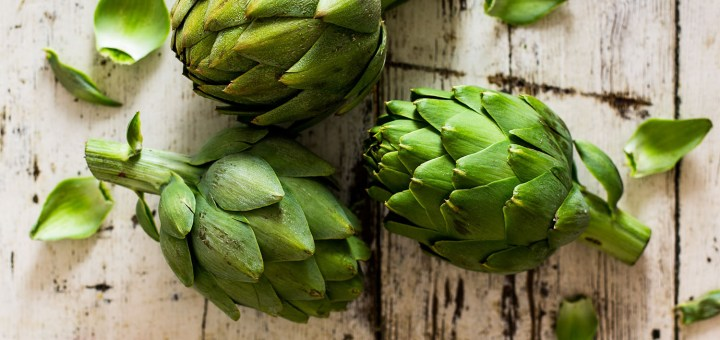 Fresh artichokes on a white washed board.