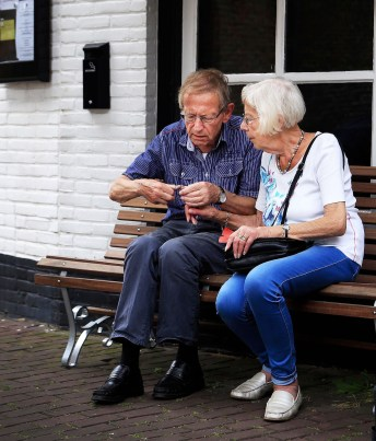 Elderly couple sitting on a bench near a white brick storefront.
