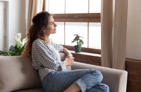 Young woman daydreaming while sitting on her could.