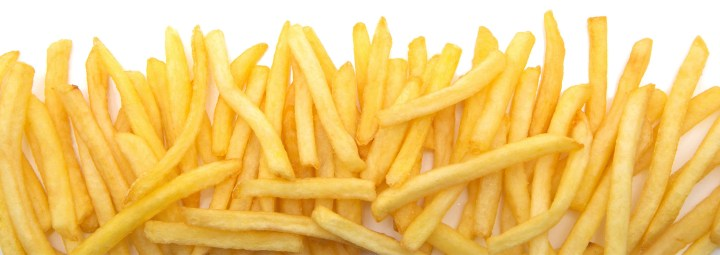 French fries, an example of nightshade vegetables, are arranged across a white background.