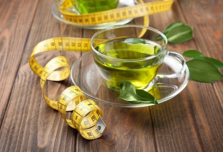 A cup of green tea and a measuring tape symbolizes one of four reasons to drink green tea.