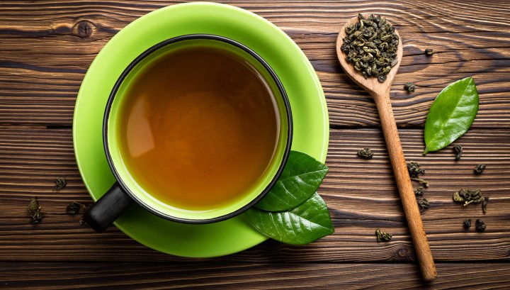 A cup of green tea on a wooden board with a spoon and scattered green tea leaves.