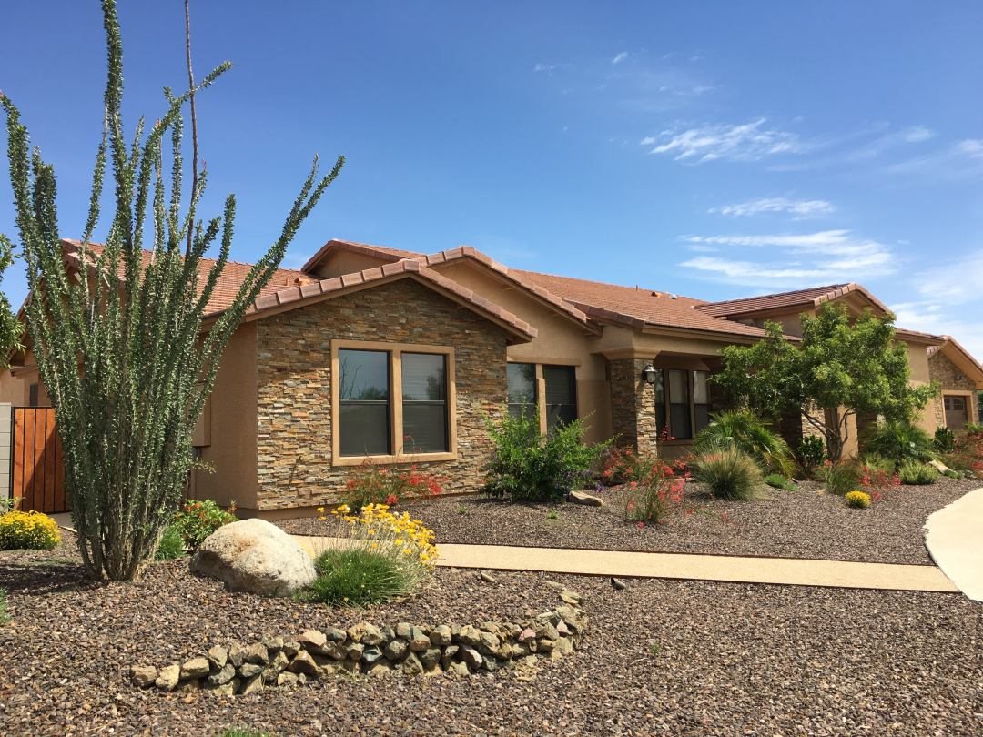A home in the desert with light brown siding and brown shingles