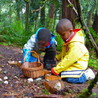 Students share items gathered in their forest classroom.