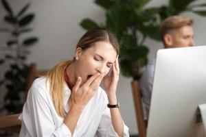 Bored Businesswoman Yawning At Workplace Feeling No Motivation