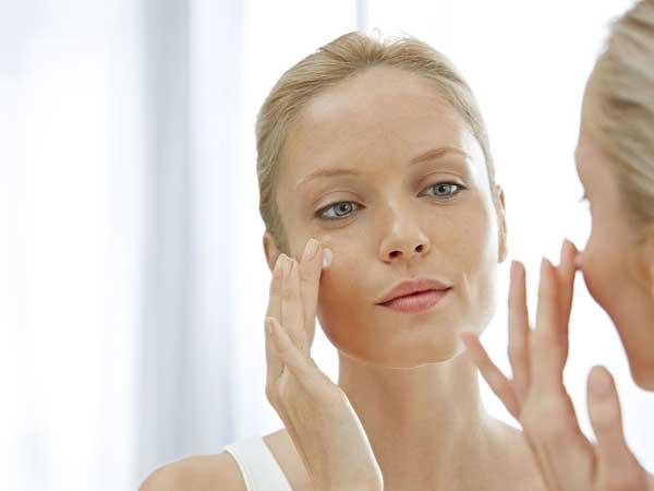 Femme qui se regarde dans un miroir posant de la crème sur son visage