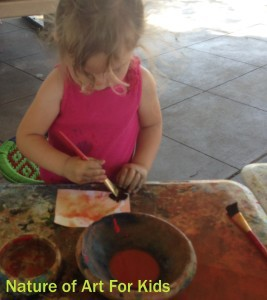 toddler painting with natural veggie paints in art class