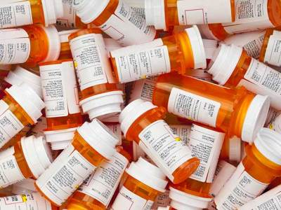a large pile of empty pill bottles