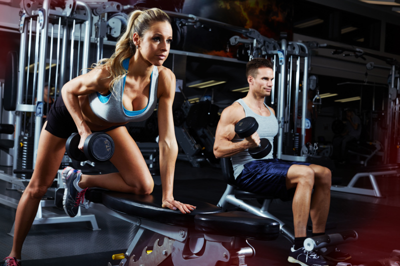 man and women in gym working out with dumbbells