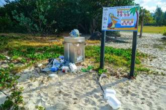 Plastic littering the sand around Mullet Bay