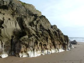 Band of white calcite exposed at the base of the cliffs in Mewslade Bay.