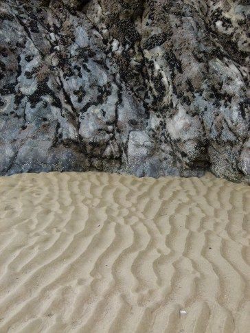 Low tide sand ripple beach pattern at the base of limestone cliffs