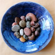 Colourful pebbles in a blue bowl