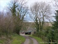 English countryside view of country lane leading to farm outbuildings