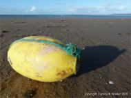 Flotsam yellow plastic fishing net float