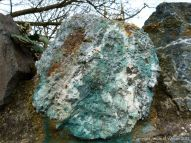 Blue copper-stained quartz rock in a stone wall