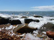 Boulders in the waves of the ebbing tide at Seatown in Dorset