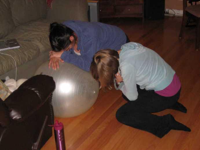 cette femme enceinte gère ses contractions avec une position adaptée sur son ballon de grossesse