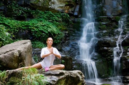 Beautiful young woman meditating with a lotus flower while doing yoga in a wonderful forest near waterfall