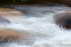 Slow shutter speed with camera motion slows the water tumbling over the rocks.