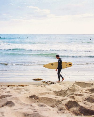 san diego surfer walking with board at pacific beach
