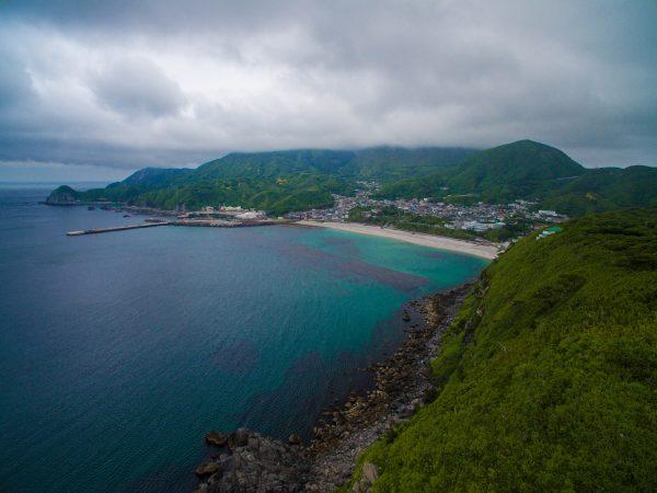 前浜海岸と集落。天上山には雲がかかる