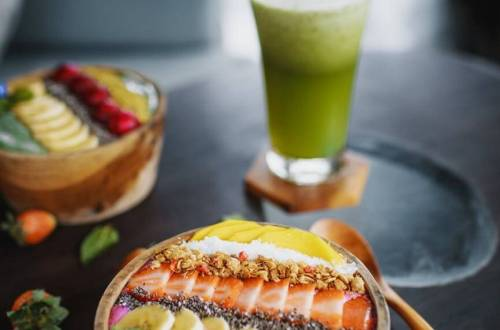 delicious smoothie in wooden bowl on cafe table