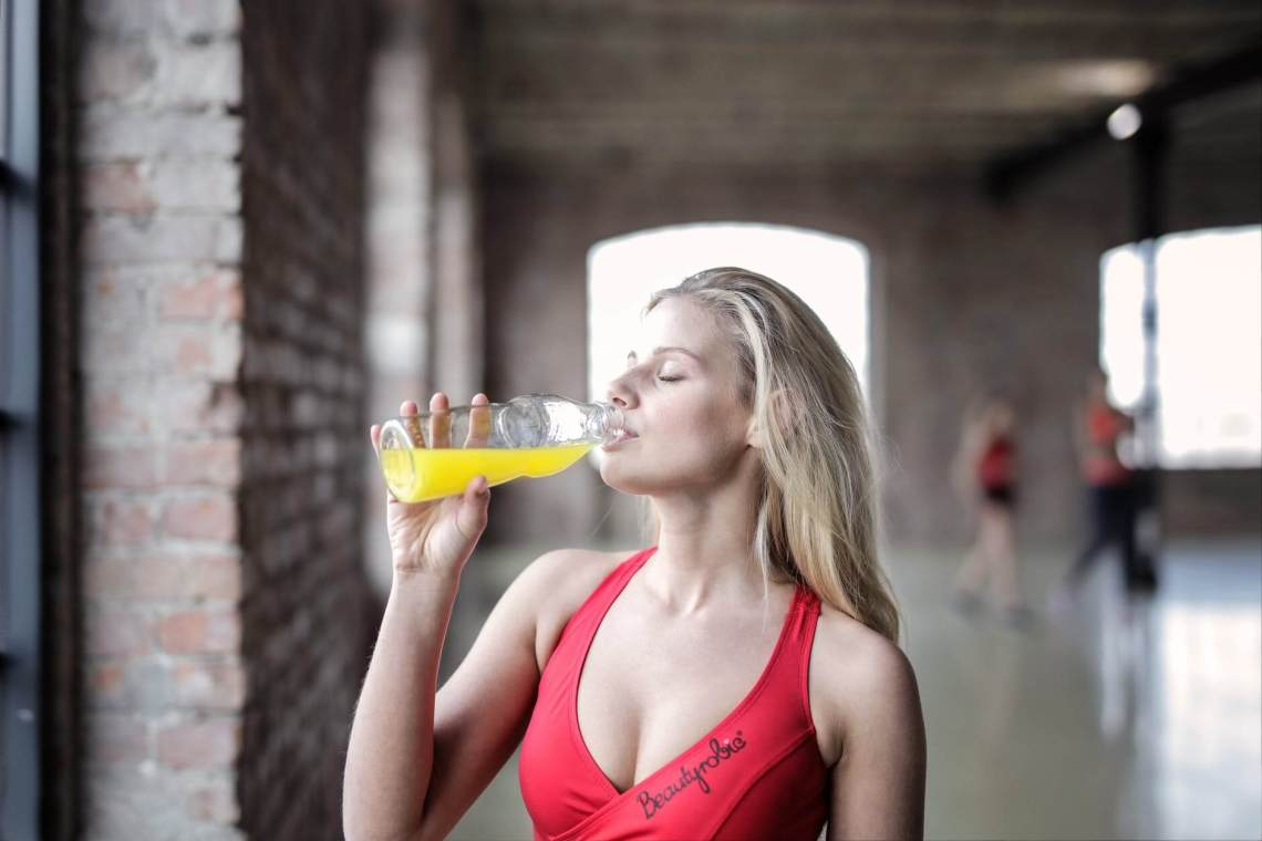 selective focus photography of woman in red tank top drinking