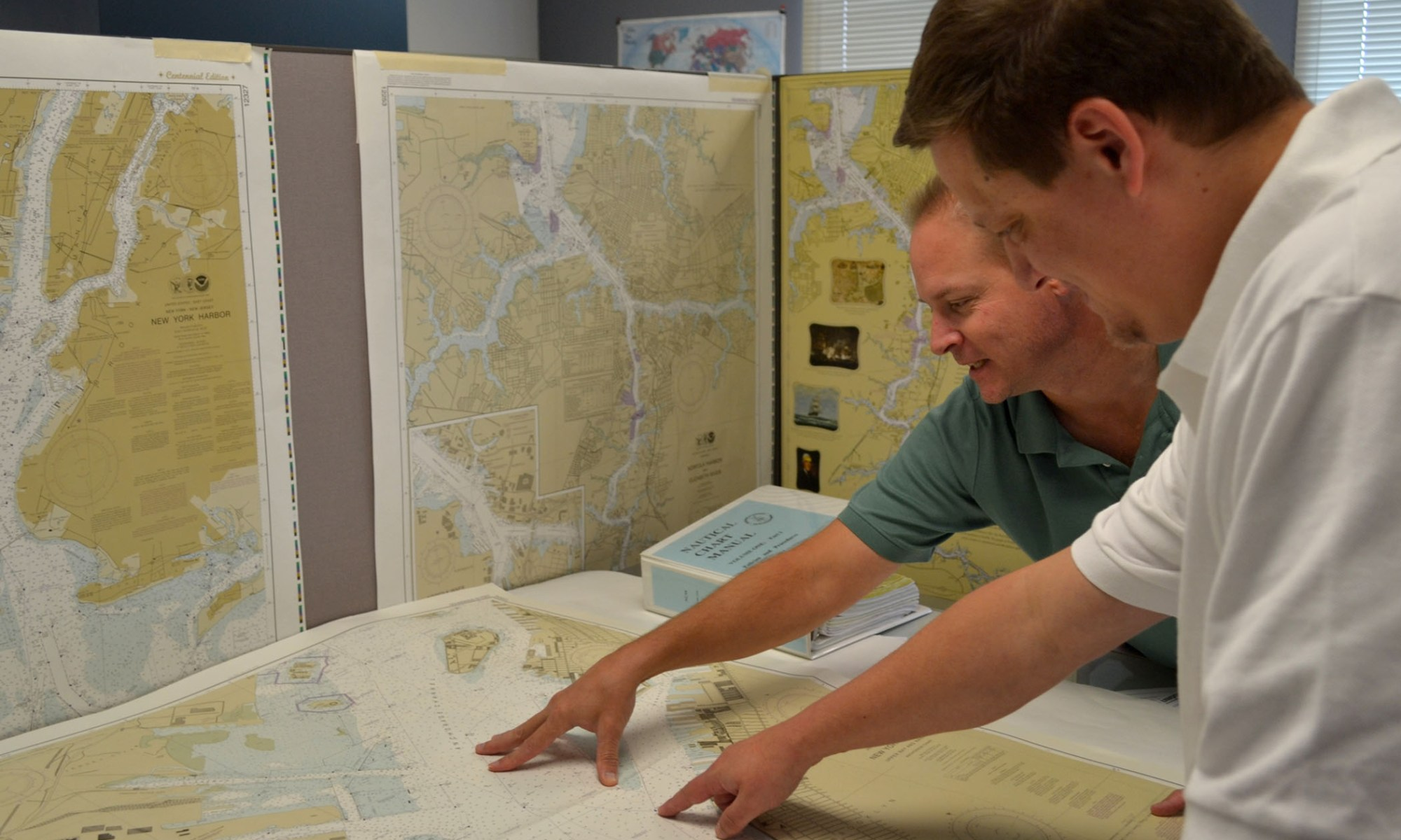 NOAA cartographers review a traditional printed nautical chart.