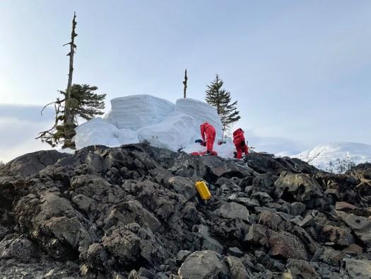 Two crew members set up the tidal benchmark on the frigid Alaskan coastline next to snow heaps.