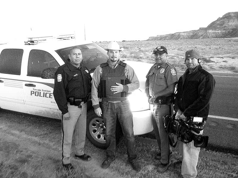 "This Oct. 2011 photo shows Navajo police officers Jason White and Virgil Smith, and ""Navajo Cops"" producer Samuel Dolan and cameraman Steve Duval. (Courtesy photo)"
