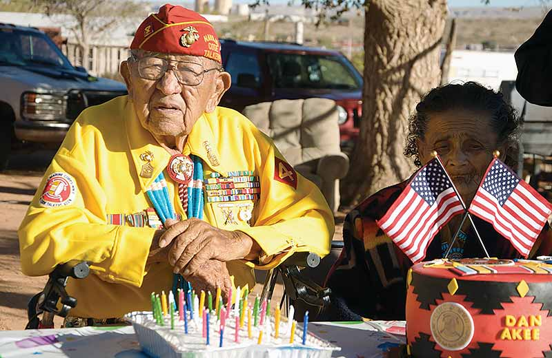 Navajo Times | Krista Allen Dressed in his yellow Code Talker shirt, Dan Akee poses for the camera before blowing out 94 candles at his home in Tónaneesdizí on Veterans Day.