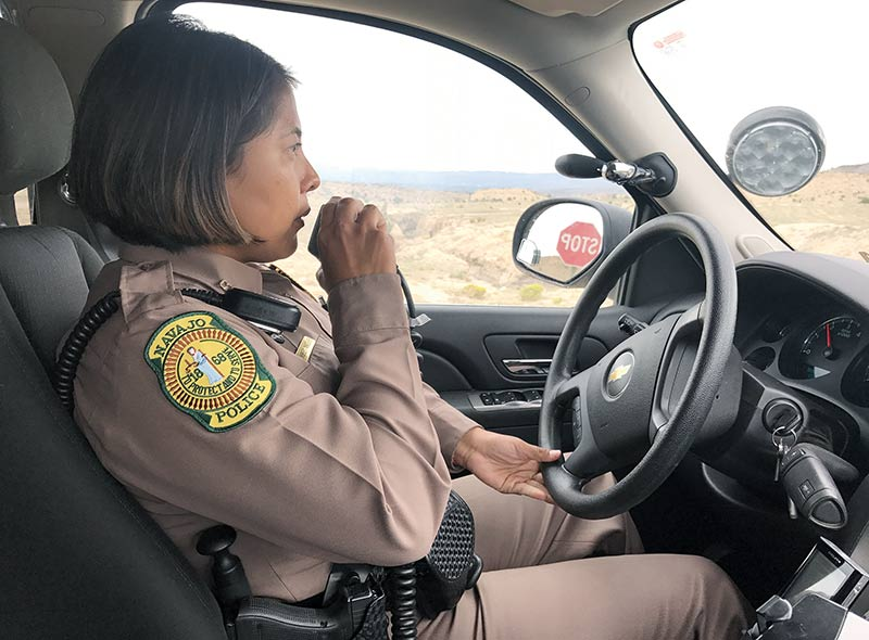 Police officer in car, driving, with radio microphone to mouth. High desert in background.