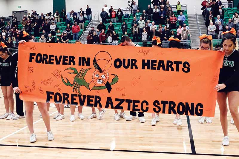 Orange banner reads: Forever in our hearts. Forever Aztec Strong. Cheerleaders bow heads.