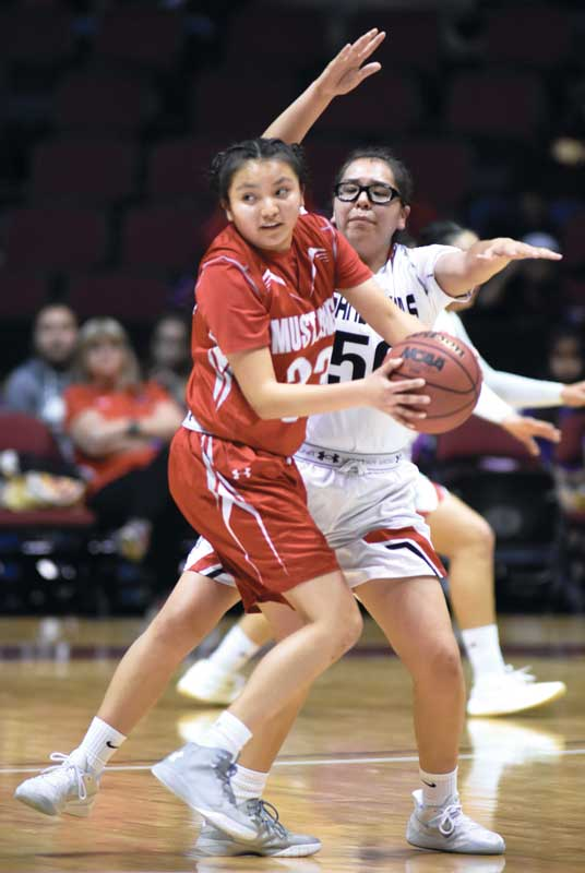 Navajo Times | Donovan Quintero Lady Mustang Lakeshia Begay looks to pass away from guarding Lady Sand Devil Jacey Salabiye Monday at the Gila River Arena in Glendale, Ariz.