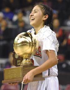 Navajo Times | Donovan Quintero St. Michael Lady Cardinal Ali Upshaw carries the team's Arizona 1A championship trophy Saturday in Prescott Valley, Ariz. The Lady Cardinals defeated the Baboquivari Lady Warriors, 60-44, to win the title.
