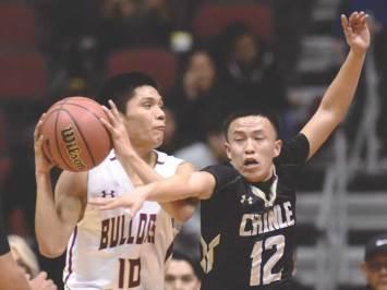 Navajo Times | Donovan Quintero Chinle's Josiah Tsosie (12) attempts to knock the ball away from Winslow Bulldog Darius James (10) Saturday during the Arizona 3A boys semifinals at the Gila River Arena in Glendale, Ariz.