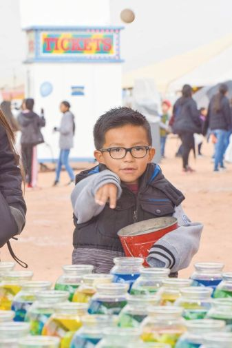Navajo Times | Krista Allen A boy tosses a ball into fish bowls in an attempt to win a goldfish during a rainy Kids Day at the 50th annual Western Navajo Fair on Oct. 11.