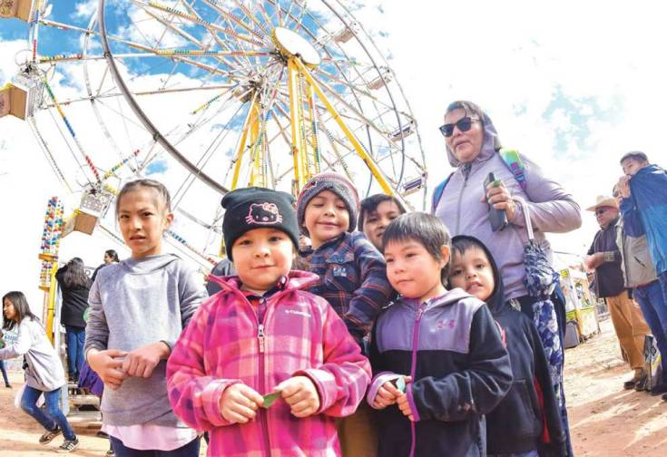 "Navajo Times | Krista Allen Eileen Deel from Kaibeto, Ariz., poses with her grandchildren for a photo in front of the ""Eli Wheel"" during Kids Day at the 50th annual Western Navajo Fair on Oct. 11."