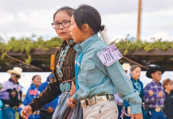 Navajo Times | Krista Allen Lemarquis Begay, 8, dances with Daelynn Begay, 10, in a round of skip dance during the 50th annual Western Navajo Fair song and dance on Friday afternoon.