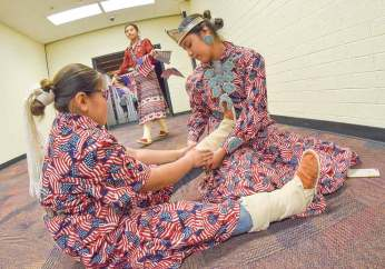 Navajo Times | Krista Allen Miss Kayenta Middle School Dawnae Yazzie helps her 9-year-old sister, D'Aaliyah, adjust the 'abaní of her kénitsaai during a Veterans Day ceremony at Monument Valley High in Tódinéeshzhee' on Nov. 12. The Yazzie sisters both wore matching patriotic outfits.