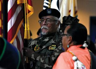 Navajo Times | Donovan Quintero A member of the Fort Defiance Veterans Organization carries the flag during the posting of the colors during a Veterans Day Gourd Dance in Fort Defiance.