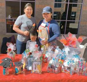 Navajo Times | Cindy Yurth Vendors Francine and Valene Hatathlie hawk their wares outside the entrance to Piñon High School's gymnasium, where the school's commencement exercises were held Saturday.