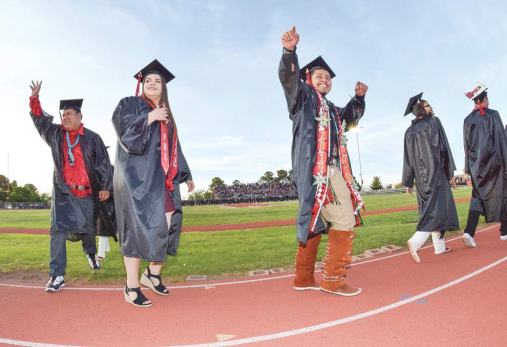 Special to the Times | Krista Allen Jeremy Tallsalt points to his family as he walks the field with his classmates during the Page High graduation at Cyclone Stadium on May 18.