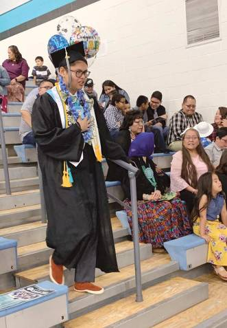 Navajo Times | Cindy Yurth Warren Billie descends the bleachers to take his place among Piñon High School's Class of 2019 Saturday. Billie plans to major in political science at Fort Lewis College and hopes to run for elected office some day.