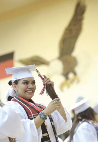 Navajo Times | Donovan Quintero Crownpoint High graduate Ba'hazhoni Crank places her tassel and feather to the opposite side of her cap to indicate she has officially graduated on Friday in Crownpoint.